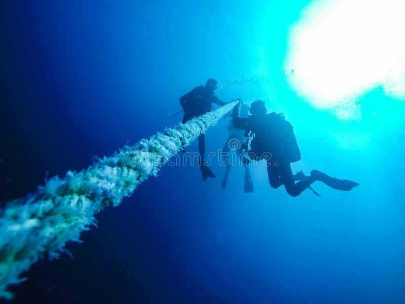 Διαφορετικό κατέβασμα σκαφάνδρων κρατώντας ένα σχοινί σε ένα ναυάγιο στο κόκκινο στοκ φωτογραφίες
