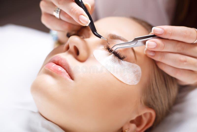 Διαδικασία επέκτασης Eyelash Μάτι γυναικών με τα μακροχρόνια eyelashes Τα μαστίγια, κλείνουν επάνω, επιλεγμένη εστίαση στοκ εικόνες