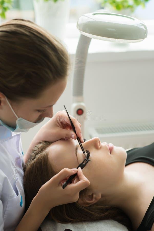 Διαδικασία επέκτασης Eyelash Μάτι γυναικών με τα μακροχρόνια eyelashes στοκ φωτογραφίες