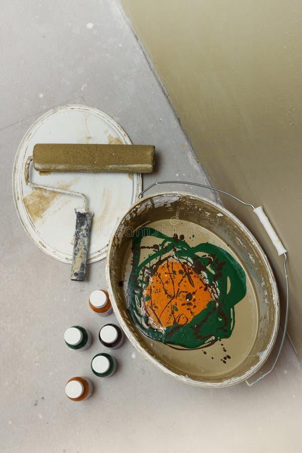 Διαδικασία το εσωτερικό χρώμα στον κάδο με τα μπουκάλια των χρωστικών ουσιών και έναν κύλινδρο από την πλευρά στοκ εικόνα με δικαίωμα ελεύθερης χρήσης