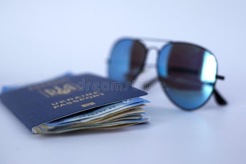 """διεθνές διαβατήριο της Ουκρανίας, των χρημάτων και των γυαλιών σε ένα άσπρο υπόβαθρο """"Η έννοια του ταξιδιού χωρίς περιττά πράγματ στοκ φωτογραφία με δικαίωμα ελεύθερης χρήσης"""