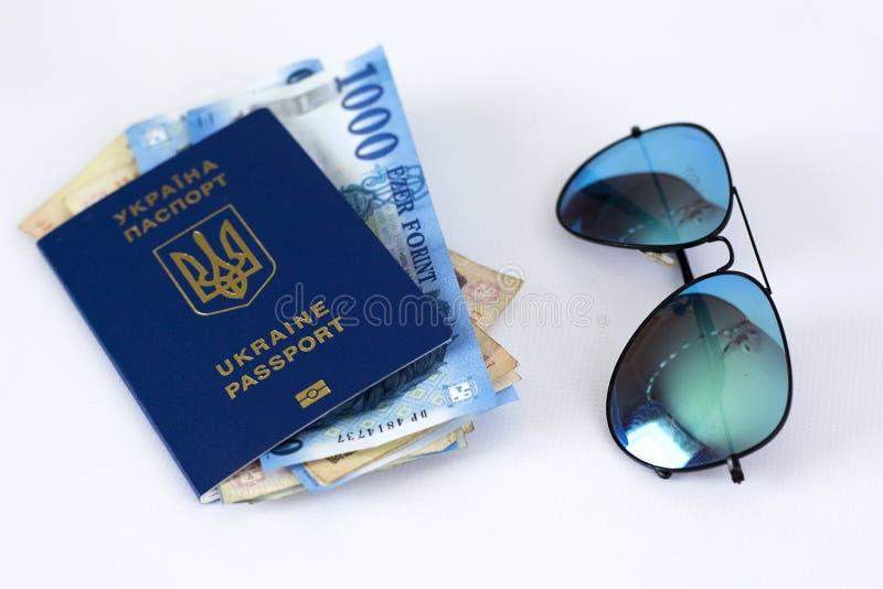 """διεθνές διαβατήριο της Ουκρανίας, των χρημάτων και των γυαλιών σε ένα άσπρο υπόβαθρο """"Η έννοια του ταξιδιού χωρίς περιττά πράγματ στοκ εικόνα με δικαίωμα ελεύθερης χρήσης"""