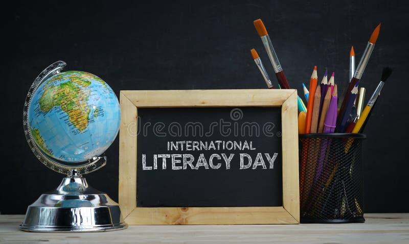 Διεθνής ημέρα βασικής εκπαίδευσης Παγκόσμια σφαίρα, σχολείο στάσιμες και Α στοκ εικόνες