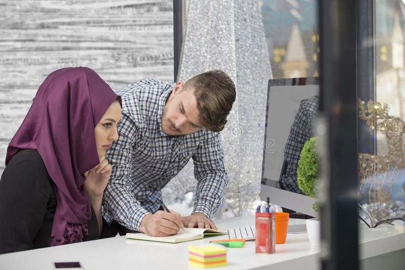 Διεθνής πολυπολιτισμική ομάδα στην εργασία: ασιατική μουσουλμανική γυναίκα και καυκάσιος άνδρας στοκ φωτογραφία με δικαίωμα ελεύθερης χρήσης