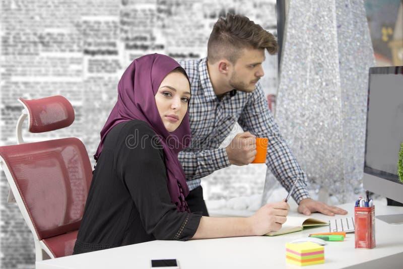 Διεθνής πολυπολιτισμική ομάδα στην εργασία: ασιατική μουσουλμανική γυναίκα και καυκάσιος άνδρας στοκ εικόνα
