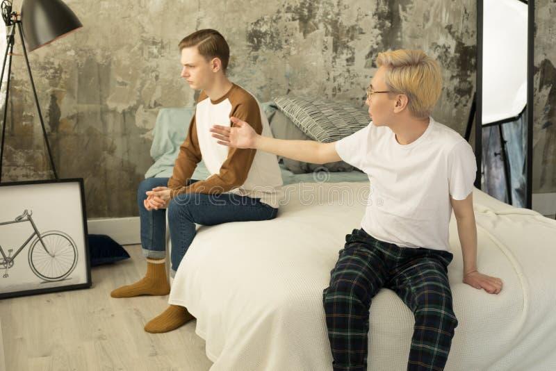 Διεθνής το ομοφυλοφιλικό ζεύγος που μαλώνει μεταξύ τους στο homa στην κρεβατοκάμαρα στοκ εικόνα