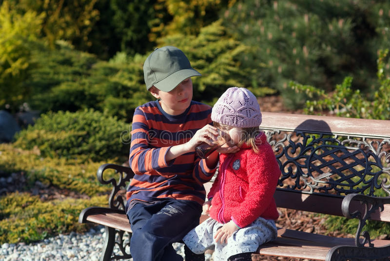 Διετές κορίτσι με τον αδελφό της στον κήπο στοκ φωτογραφία