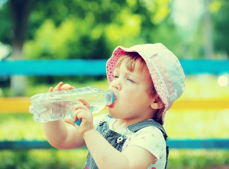 Διετή ποτά παιδιών από το πλαστικό μπουκάλι στοκ εικόνα με δικαίωμα ελεύθερης χρήσης
