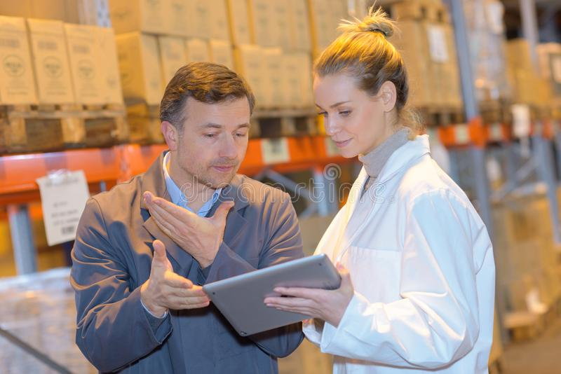 Διευθυντές αποθηκών εμπορευμάτων που εξετάζουν το PC ταμπλετών στη μεγάλη αποθήκη εμπορευμάτων στοκ εικόνα