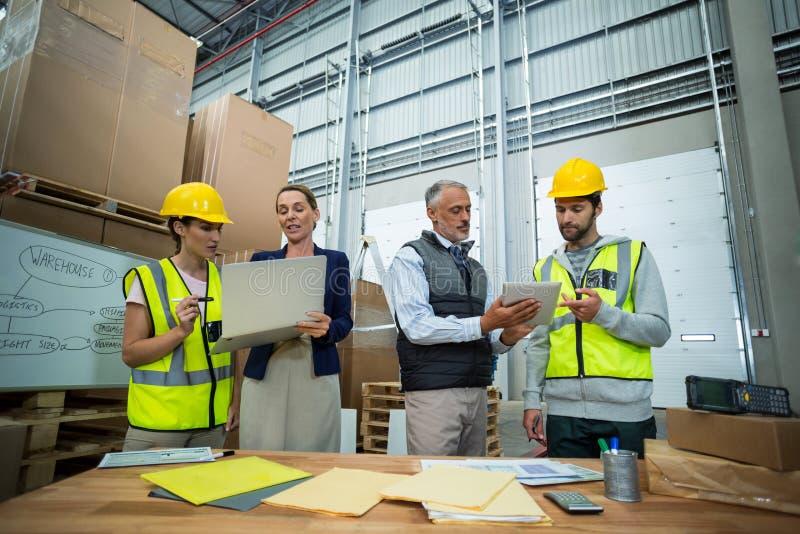 Διευθυντές και εργαζόμενοι αποθηκών εμπορευμάτων που συζητούν με το lap-top και την ψηφιακή ταμπλέτα στοκ φωτογραφίες