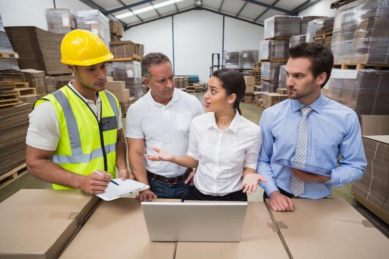 Διευθυντές και εργαζόμενος αποθηκών εμπορευμάτων που μιλούν από κοινού στοκ εικόνες