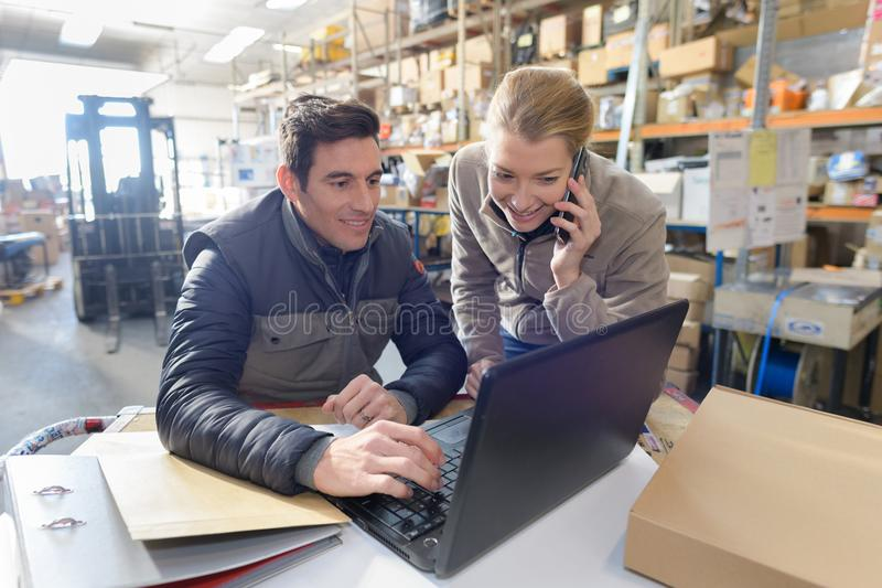 Διευθυντές που εργάζονται στο lap-top και που μιλούν στο τηλέφωνο στην αποθήκη εμπορευμάτων στοκ φωτογραφίες με δικαίωμα ελεύθερης χρήσης