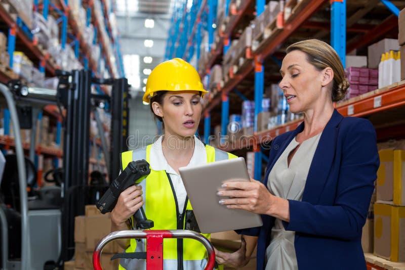 Διευθυντής αποθηκών εμπορευμάτων με την αλληλεπιδρώντας γυναίκα εργαζόμενος πέρα από την ψηφιακή ταμπλέτα στοκ φωτογραφία
