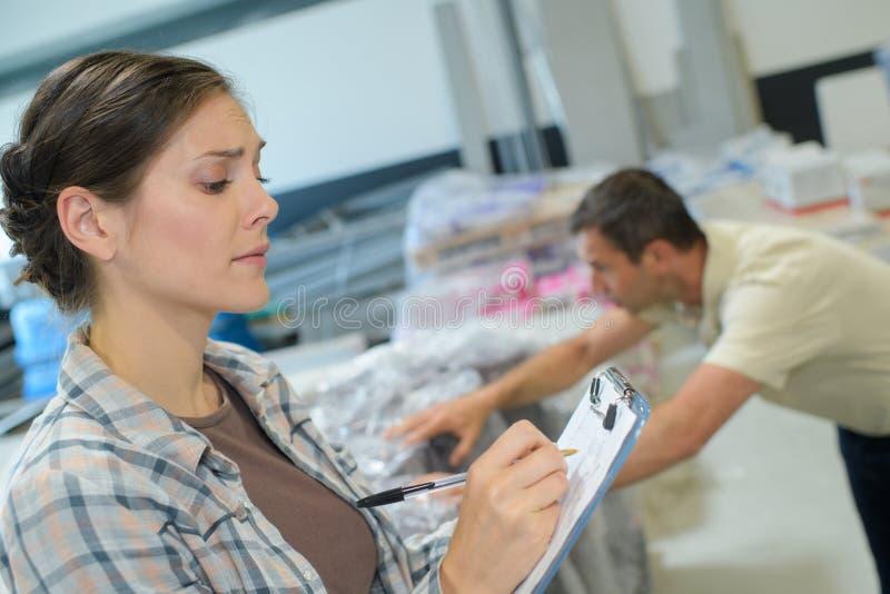 Διευθυντής αποθηκών εμπορευμάτων που ελέγχει τον κατάλογο στη μεγάλη αποθήκη εμπορευμάτων στοκ φωτογραφία με δικαίωμα ελεύθερης χρήσης