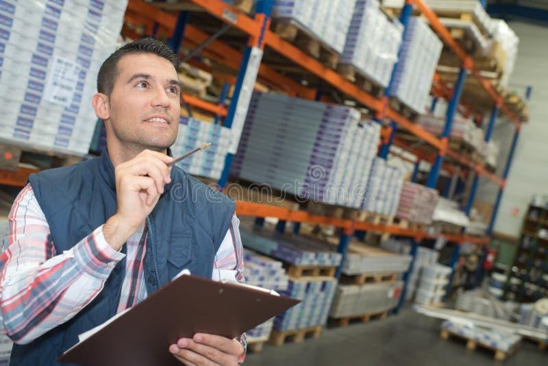 Διευθυντής αποθηκών εμπορευμάτων που ελέγχει τον κατάλογο στη μεγάλη αποθήκη εμπορευμάτων στοκ φωτογραφίες