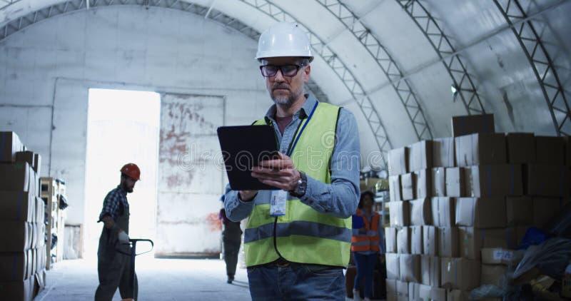 Διευθυντής αποθηκών εμπορευμάτων που εξετάζει τη κάμερα στοκ φωτογραφία