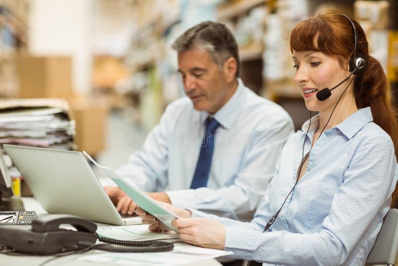 Διευθυντής αποθηκών εμπορευμάτων που εργάζεται στο γραφείο της που φορά την κάσκα στοκ εικόνες με δικαίωμα ελεύθερης χρήσης