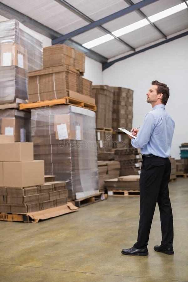 Διευθυντής αποθηκών εμπορευμάτων που ελέγχει τον κατάλογό του στοκ εικόνα