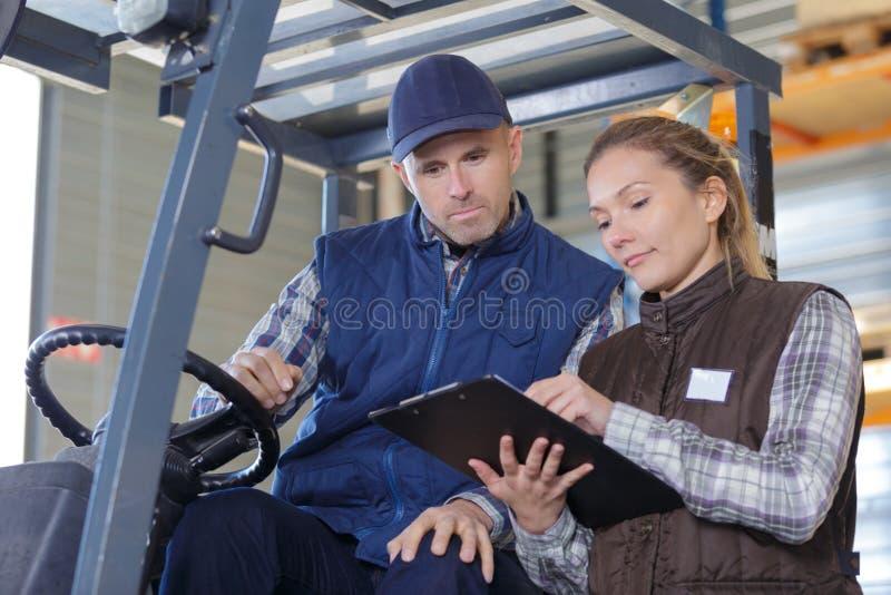 Διευθυντής αποθηκών εμπορευμάτων που μιλά με forklift τον οδηγό στη μεγάλη αποθήκη εμπορευμάτων στοκ φωτογραφίες με δικαίωμα ελεύθερης χρήσης