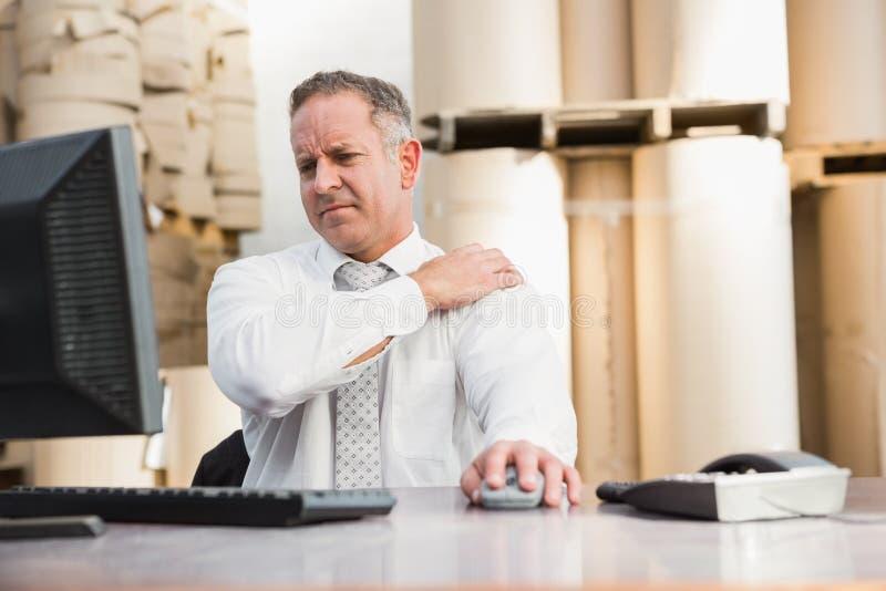 Διευθυντής αποθηκών εμπορευμάτων που πάσχει από τον πόνο ώμων στοκ εικόνα