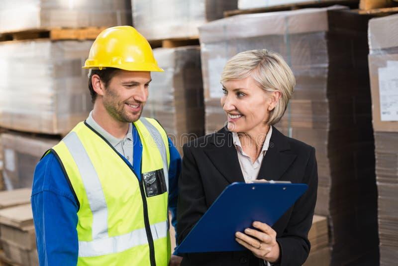 Διευθυντής αποθηκών εμπορευμάτων που παρουσιάζει περιοχή αποκομμάτων στο συνάδελφό της στοκ εικόνα με δικαίωμα ελεύθερης χρήσης
