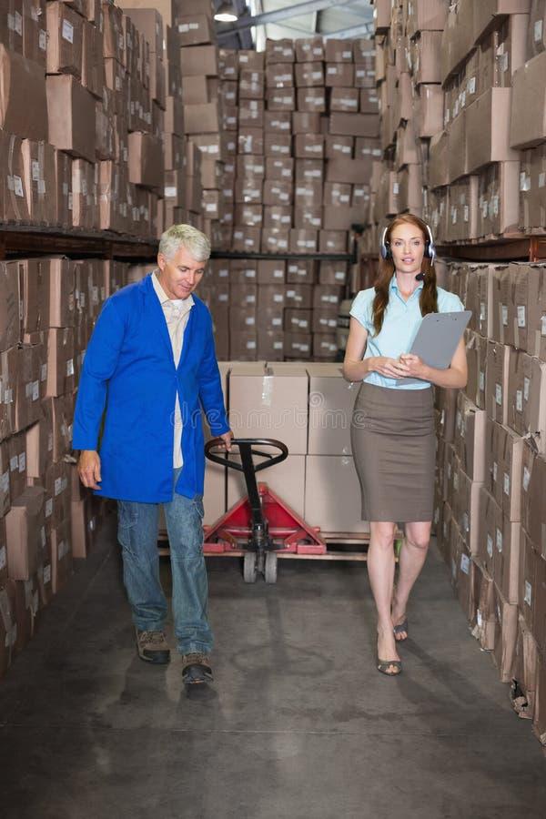 Διευθυντής αποθηκών εμπορευμάτων που περπατά με τον επιστάτη που τραβά το καροτσάκι στοκ εικόνες