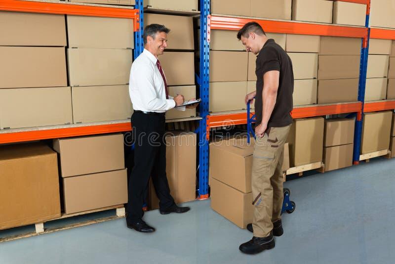 Διευθυντής και εργαζόμενος στην αποθήκη εμπορευμάτων στοκ φωτογραφία με δικαίωμα ελεύθερης χρήσης