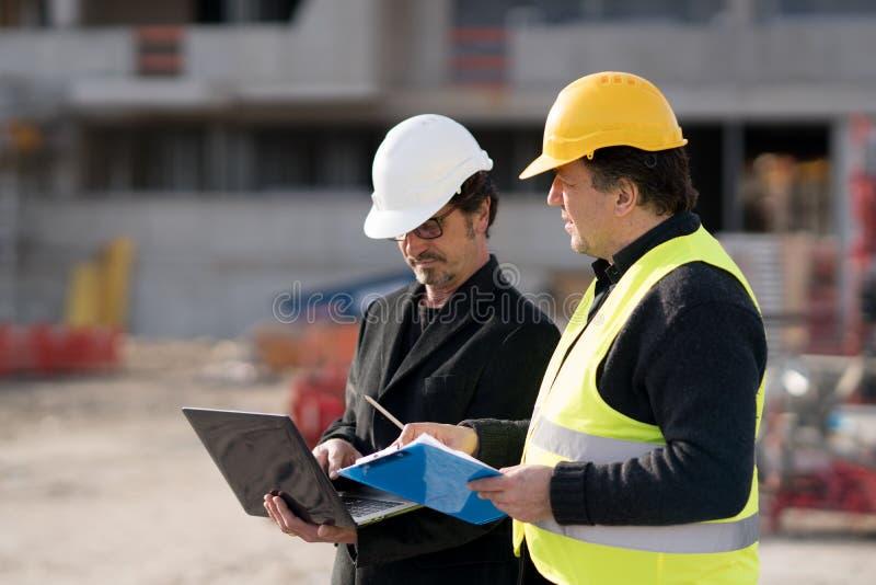 Διευθυντής και μηχανικός κατασκευής στην εργασία για το εργοτάξιο οικοδομής στοκ εικόνα