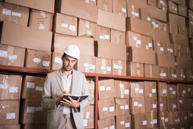Διευθυντής με το ημερολόγιο ενάντια στα κιβώτια στην αποθήκη εμπορευμάτων στοκ φωτογραφία με δικαίωμα ελεύθερης χρήσης