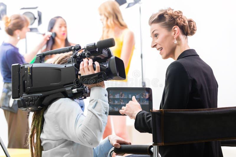 Διευθυντής που δίνει την κατεύθυνση καμεραμάν για την τηλεοπτική παραγωγή στοκ εικόνες