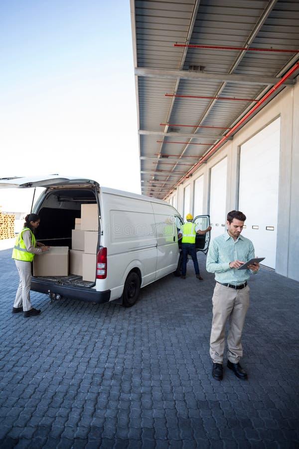 Διευθυντής που εργάζεται στους εργαζομένους ταμπλετών και αποθηκών εμπορευμάτων που φορτώνουν τα κουτιά από χαρτόνι στοκ εικόνες