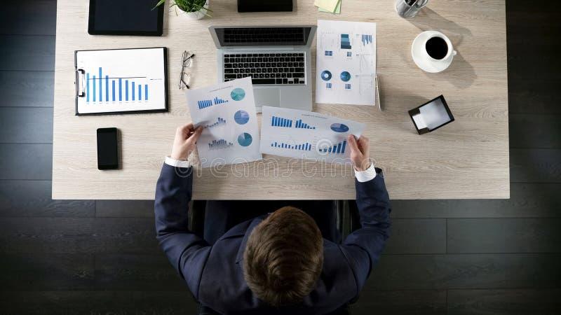 Διευθυντής που συγκρίνει τις στατιστικές επιχείρησης με τα στοιχεία κεντρικών γραφείων όσον αφορά το lap-top, τοπ άποψη στοκ φωτογραφία με δικαίωμα ελεύθερης χρήσης