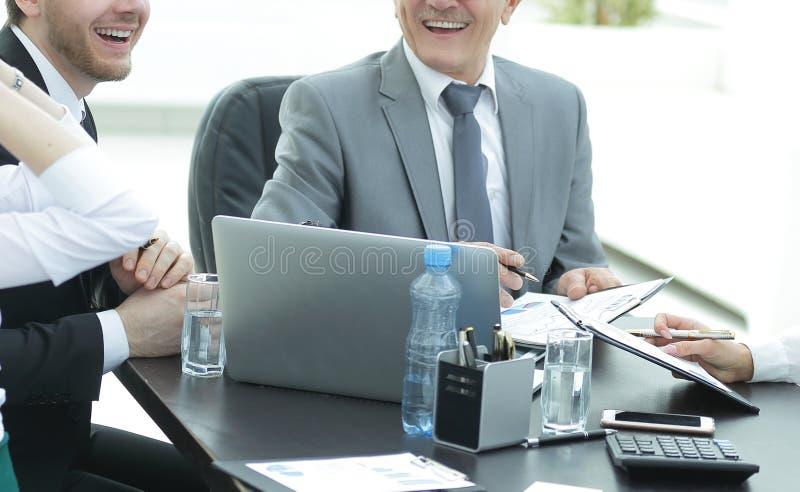 Διευθυντής που συζητά τα ζητήματα εργασίας με τους βοηθούς του πίσω από ένα γραφείο στοκ φωτογραφία