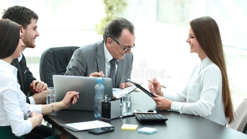 Διευθυντής που συζητά τα ζητήματα εργασίας με τους βοηθούς του πίσω από ένα γραφείο στοκ φωτογραφία με δικαίωμα ελεύθερης χρήσης