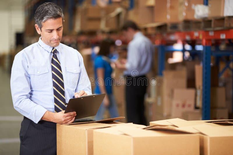 Διευθυντής στην αποθήκη εμπορευμάτων που ελέγχει τα κιβώτια στοκ εικόνα με δικαίωμα ελεύθερης χρήσης