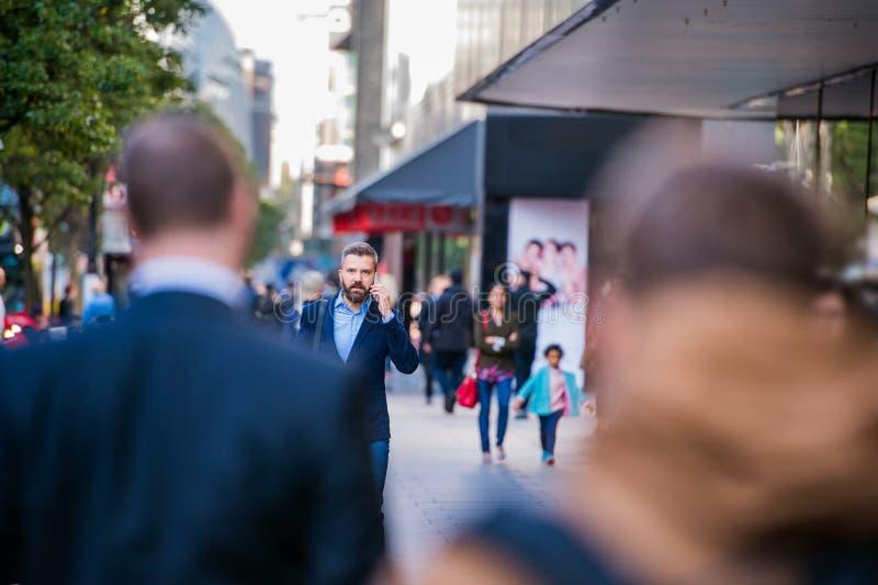 Διευθυντής Hipster με το έξυπνο τηλέφωνο που περπατά στην οδό στοκ εικόνες