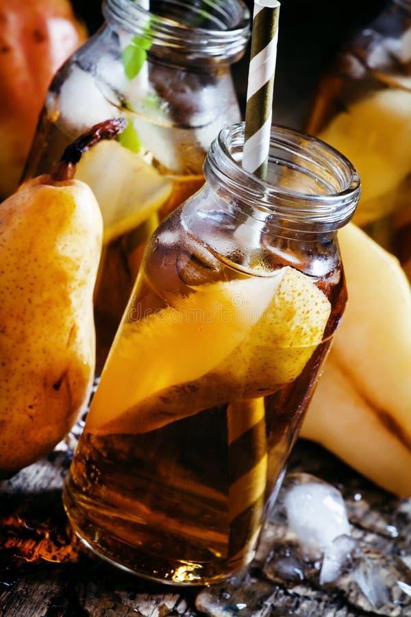 Διευκρινισμένος χυμός αχλαδιών με τον πάγο και τις φέτες των φρούτων στο γυαλί bottl στοκ εικόνα