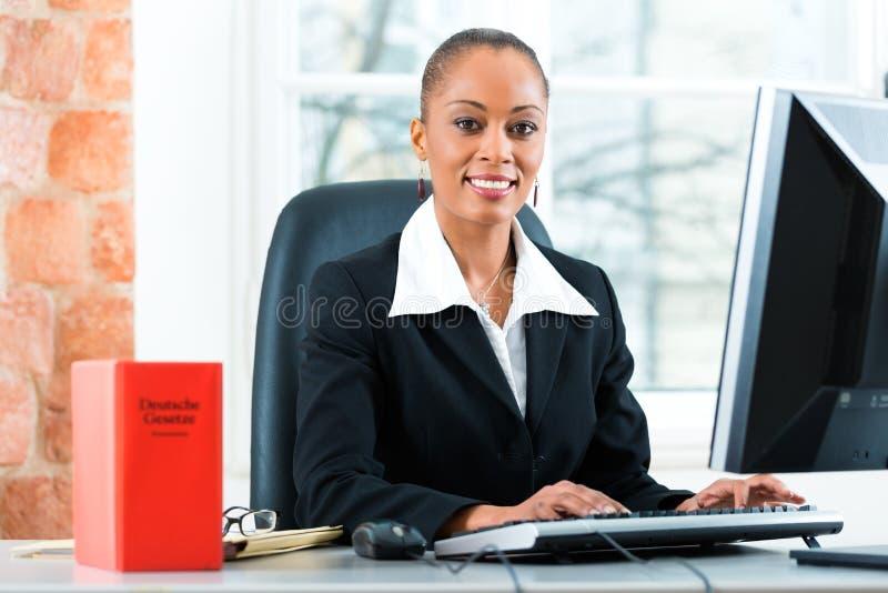 Δικηγόρος στο γραφείο της με το βιβλίο νόμου στον υπολογιστή στοκ φωτογραφία
