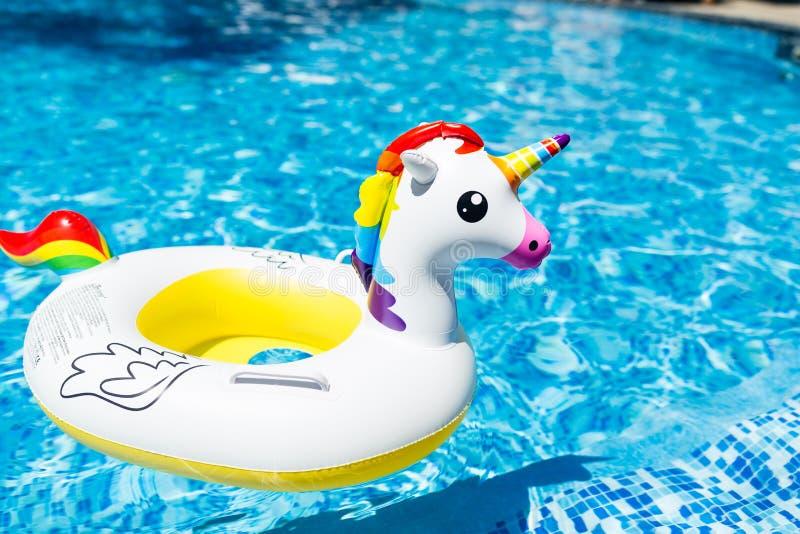 Διογκώσιμος ζωηρόχρωμος λευκός μονόκερος στην πισίνα Θερινός χρόνος στην πισίνα με τα πλαστικά παιχνίδια Θερινές διακοπές, στοκ φωτογραφία με δικαίωμα ελεύθερης χρήσης