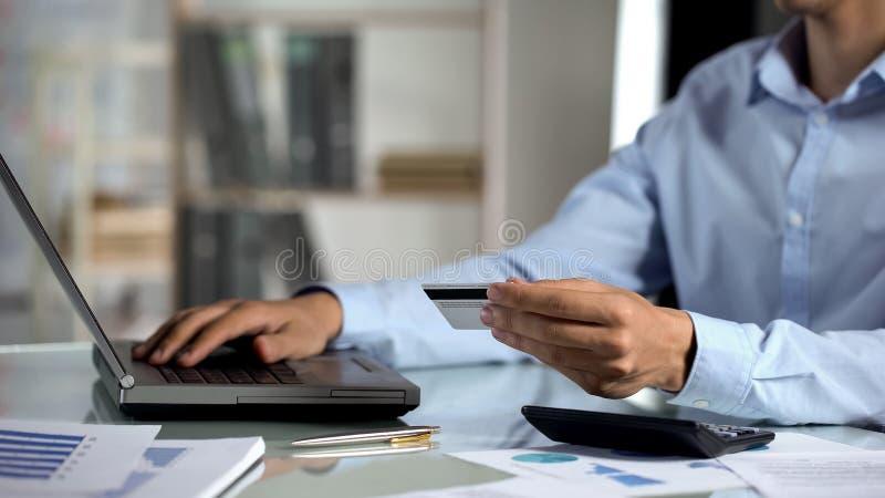 Διοικητής που εισάγει τον αριθμό καρτών στο lap-top γραφείων, ψωνίζοντας on-line, κατάθεση στοκ εικόνες
