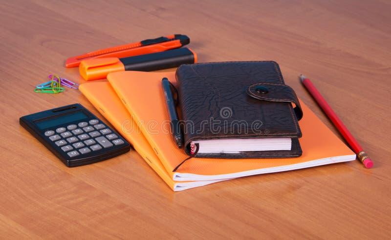 Διοργανωτής, σημειωματάριο, στυλός, μολύβι, δείκτης, κόπτης και υπολογιστής στον υπολογιστή γραφείου στοκ εικόνες με δικαίωμα ελεύθερης χρήσης
