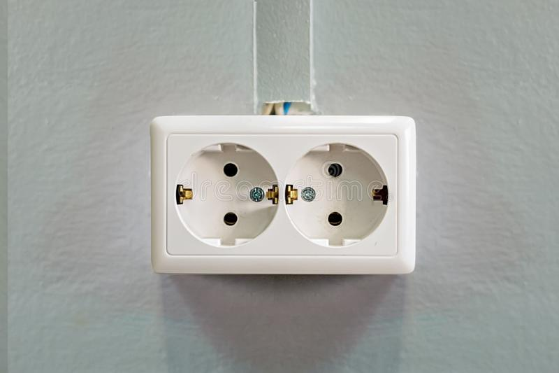 Διπλή άσπρη υποδοχή σε έναν γκρίζο τοίχο Κινηματογράφηση σε πρώτο πλάνο Μπροστινή όψη Να στηρίξει και καλωδιακό κανάλι στοκ εικόνες με δικαίωμα ελεύθερης χρήσης