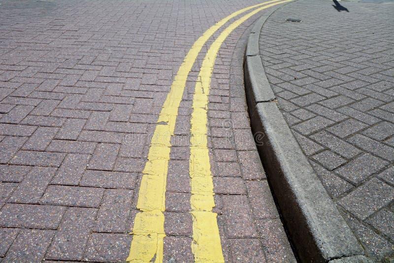 Διπλή κίτρινη γραμμή που χρωματίζεται στο δρόμο στοκ εικόνες