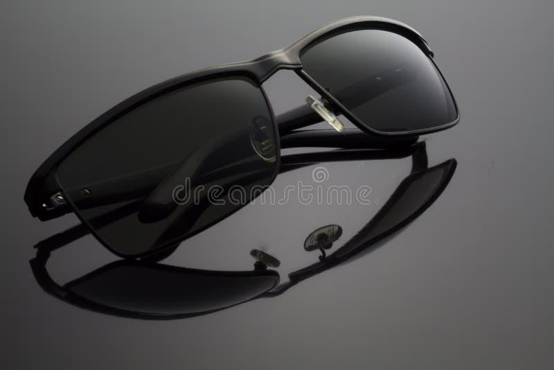 Διπλωμένα μαύρα γυαλιά ηλίου στο μαύρο υπόβαθρο στοκ εικόνες