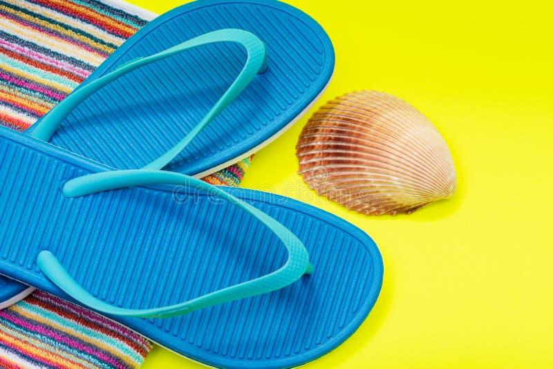 Διπλωμένες ζωηρόχρωμες ριγωτές οργανικές πετσέτες παραλιών βαμβακιού, μπλε πτώσεις και θάλασσα Shell κτυπήματος φωτεινό σε κίτριν στοκ εικόνα