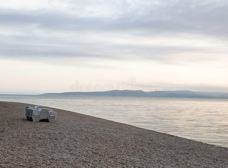 Διπλωμένες καρέκλες παραλιών σε μια παραλία χαλικιών ενάντια στο σκηνικό μιας ήρεμης καθαρής θάλασσας, των βουνών και του ηλιοβασ στοκ εικόνες