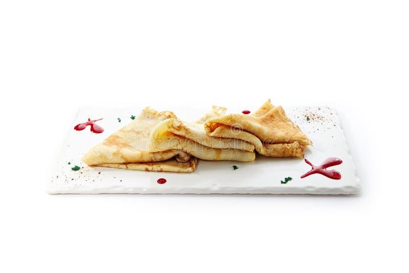 Διπλωμένος Crepes, Blini ή τηγανίτες στο άσπρο πιάτο στοκ εικόνες