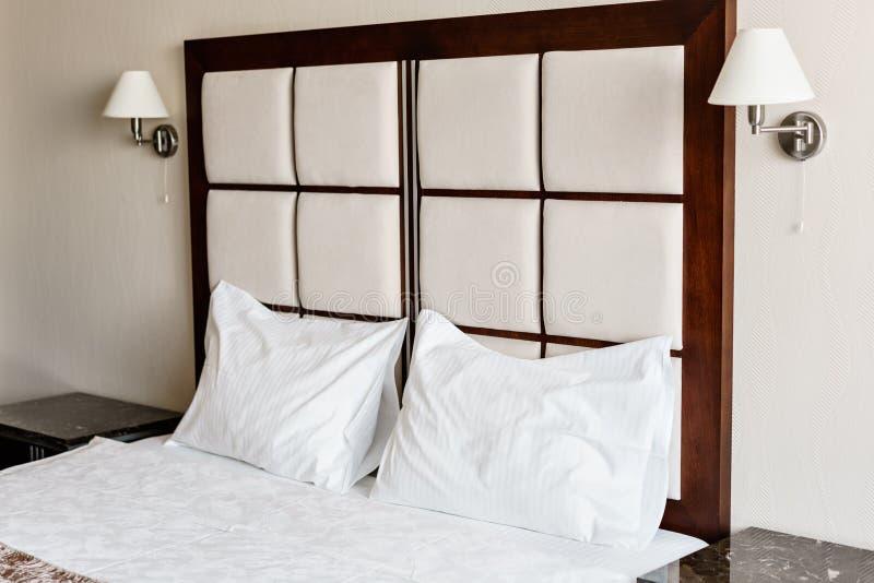διπλός σύγχρονος κρεβατ Άνετα μαλακά άσπρα μαξιλάρια σε ένα κρεβάτι Εσωτερικά δωμάτια ενός διαμερίσματος ή ενός ξενοδοχείου στοκ εικόνες με δικαίωμα ελεύθερης χρήσης
