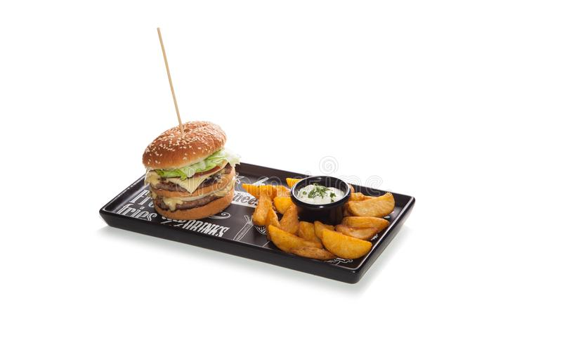 Διπλό χάμπουργκερ επάνω με τις τηγανιτές πατάτες στο πιάτο με τη σαλάτα στο whi στοκ φωτογραφία με δικαίωμα ελεύθερης χρήσης