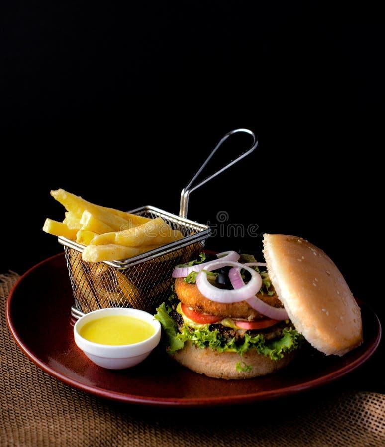 Διπλό BBQ Burger βόειου κρέατος με τις τηγανιτές πατάτες & τη σάλτσα εμβύθισης στοκ εικόνα